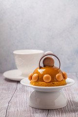 Cake of mousses and caramel on a gray background, horizontally