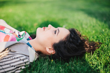 Beautiful woman lying on grass in a park