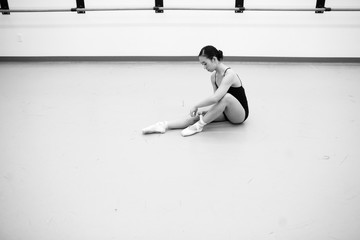 Woman putting on ballet shoes
