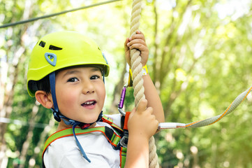 Happy little boy passing the cable route high among trees, climbing and playing, extreme sport in adventure park