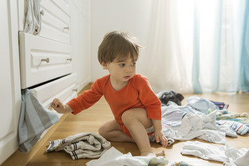1 year old boy throws out clothes from wooden furniture at home