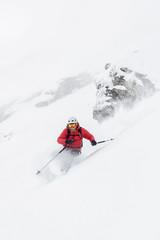 Skier taking a sharp turn splashing with snow