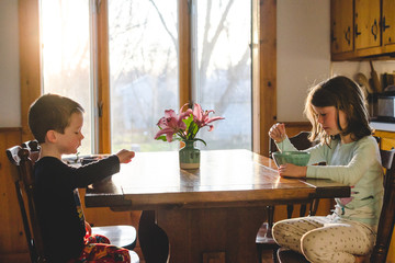 Two children eating breakfast at the table
