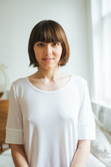 Indoor Portrait of Young Pretty Caucasian Woman in White T-Shirt