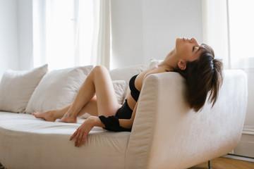 Sensual Caucasian Brunette in Black Underwear in Erotic Pose on White Sofa