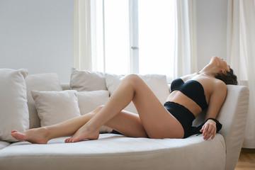 Sensual Caucasian Brunette in Black Underwear in Erotic Pose on Sofa
