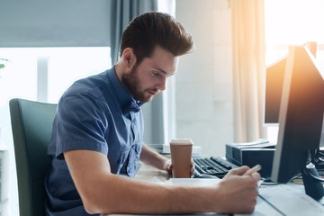 creative male office worker with coffee writing