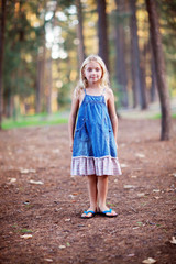 Little Blonde Girl WEaring Denim Dress Standing In The Woods
