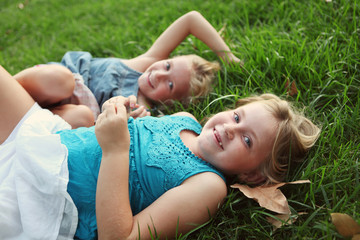 Sisters Laying In Grass Laughing