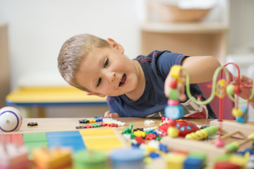 Smiling caucasian boy curiously looks in toy