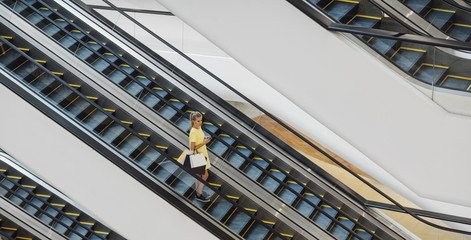 Caucasian Woman on an Escalator in the Shopping Mall