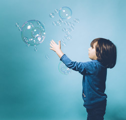 5 year old boy trying to catch soap bubbles