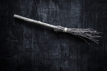 Ancient natural, old wooden broom created from tree branches, which wiped rooms, yards and streets. Witch's broom on the dark, wooden background. Traditional Halloween symbol. Retro vintage style.