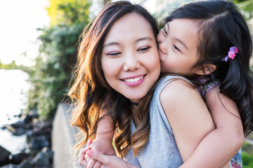 Happy Asian girl kissing her mother