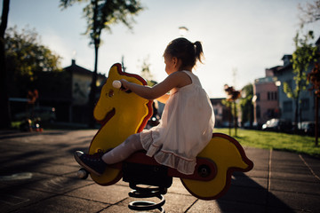 Portrait of little girl playing on a wooden toy horse