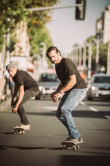 Two skateboarders riding skateboard slope on the city streets