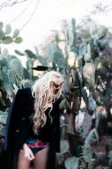 Blonde girl standing in front of cactus