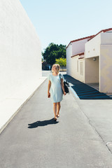 Young Blonde Pregnant Woman In Light Blue Dress Walking Along White Washed Alley