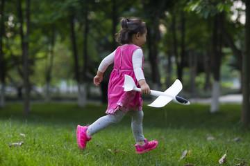 lovely little asian girl running outdoor in the park