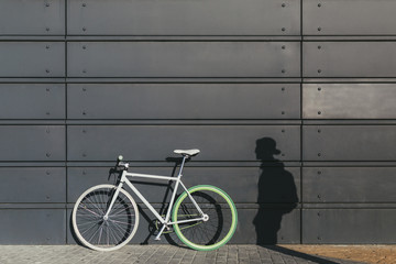 Fixie Bicycle Leaning on a Metallic Wall Besides a Man Shadow