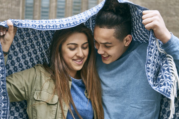 Teenage couple covering with scarf