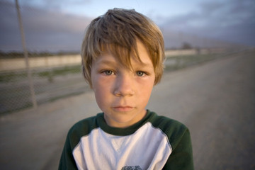 Wide Angle View Of Boy on Dirt Road