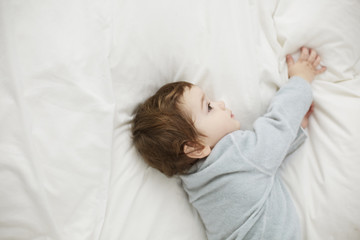 Toddler in a dreamy mood lying on the bed