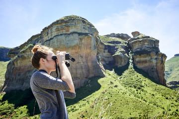 Young woman viewing a mountainous landscape through binoculars