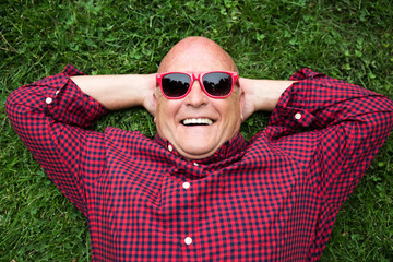 Smiling man laying on grass wearing sunglasses