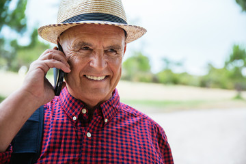 Stylish senior man in hat talking on cell phone