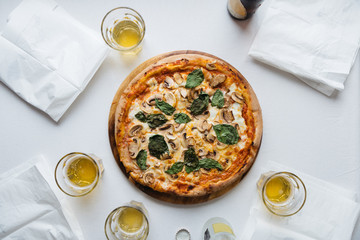 Overhead view of a pizza served with beer on the table