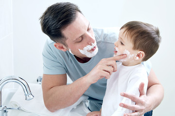 Father and son using shaving cream