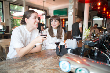 Young women drinking wine at bar