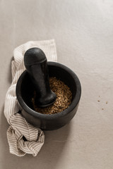A pestle and mortar with cumin seeds