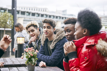 Teenagers sitting at outdoor table