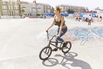 Young woman riding bicycle at skate park