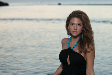 Woman in a black dress with turquoise necklace.