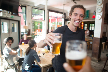 Young man making celebratory toast in bar