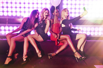 Young women sitting together at nightclub