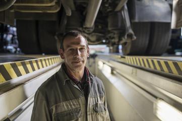 Mechanic in pit beneath truck