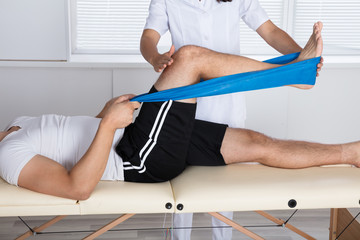 Physiotherapist Helping Patient While Exercising