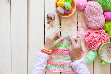 A woman knits a bright colored canvas with spokes. Hands close-up.