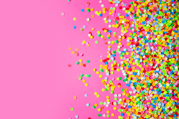 Frame made of colored confetti. Pink background.