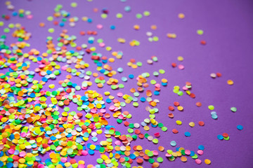 Frame made of colored confetti. Lilac and violet background.