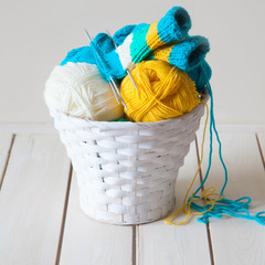 Woolen yarn in coils and tangles in a white basket. A table made of white wood.