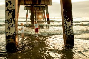 Kids looking under pier