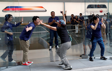 Apple fan Kimura who has been waiting in line to purchase new Apple Watch, reacts with Apple Store staff as she enters the Apple Store in Tokyo's Omotesando shopping district