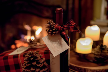 romantic bottle of wine and Christmas presents by cozy fireplace