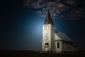 horizontal image of a bright light shining on an old white country church in the late evening and night time.