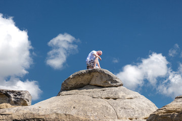 horizontal image of a middle aged caucasian man sitting on a tall boulder in the summer time taking time for solitude  under a bright blue sky with white clouds floating by in the summer time